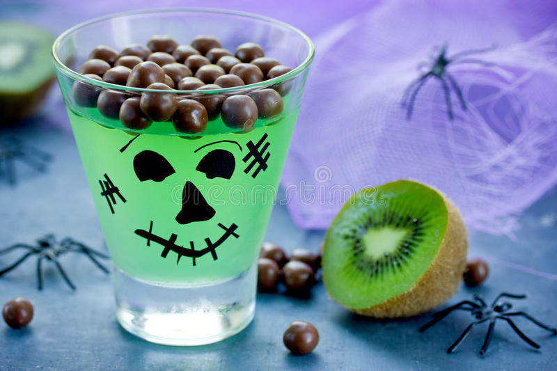 Frankenstein kiwi jelly in glass with sweet chocolate balls for royalty free stock photo