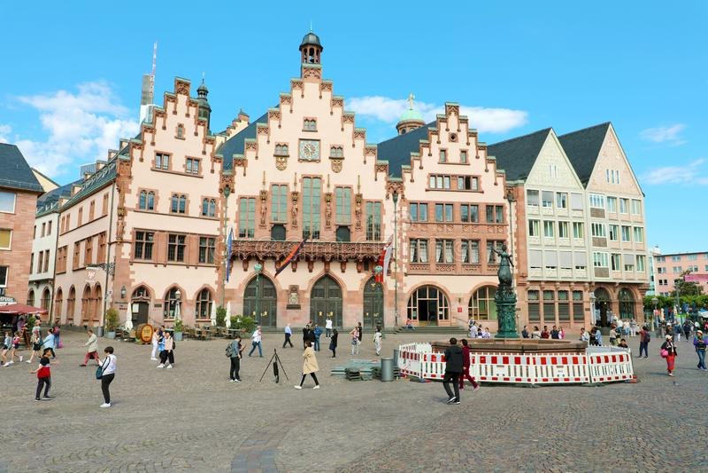 FRANKFURT, DEUTSCHLAND - 13. JUNI 2019: Touristen in Romerberg-Quadrat mit der Rathaus- und Gerechtigkeitsstatue auf blauem Himme stockbilder