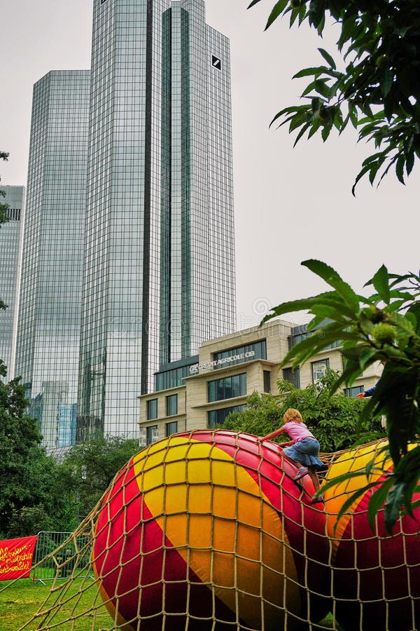 Little girl climbs huge beach balls in the urban jungle of downtown Frankfurt stock image
