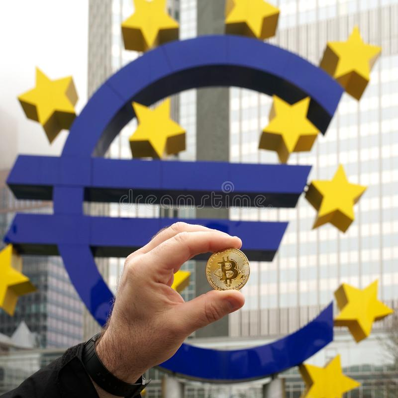 Hand holding a Bitcoin coin next to the Euro sign in Frankfurt Germany stock image