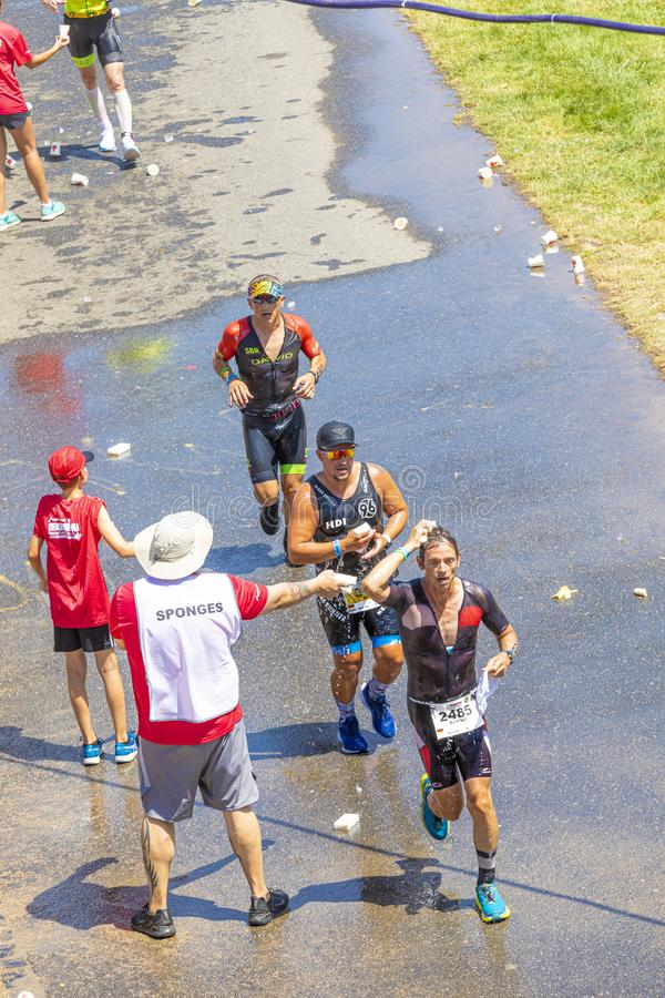 athletes drink mineral water or get a shower while running at the frankfurt ironman 2019. Because of the heat the caterin stations royalty free stock images