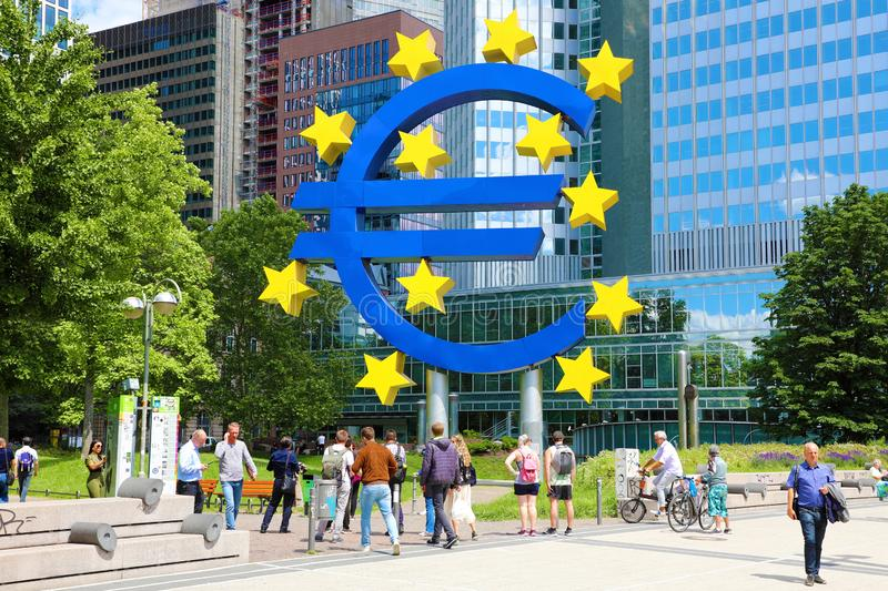 FRANKFURT, GERMANY - JUNE 13, 2019: people walking under euro sign in Frankfurt. The European Central Bank administers monetary royalty free stock images