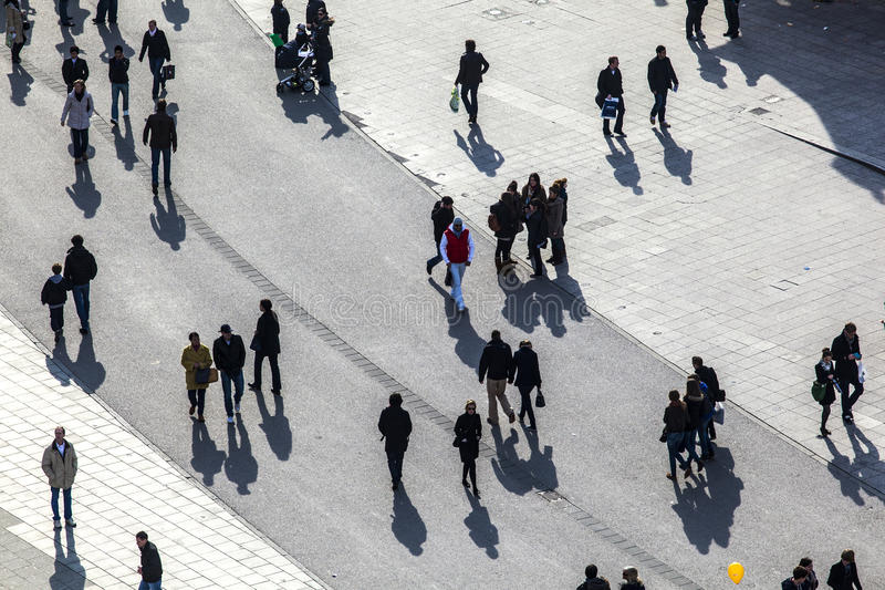 People walking at the street with long shadows stock photography