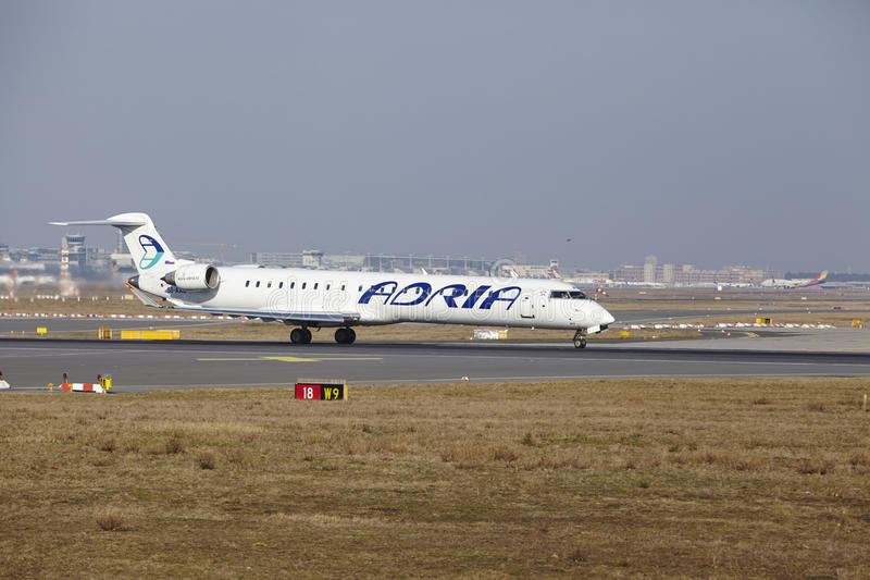 Frankfurt International Airport – Adria Airways Canadair 900 takes off. The Adria Airways Canadair CRJ-900LR with identification S5-AAU takes off at royalty free stock photo