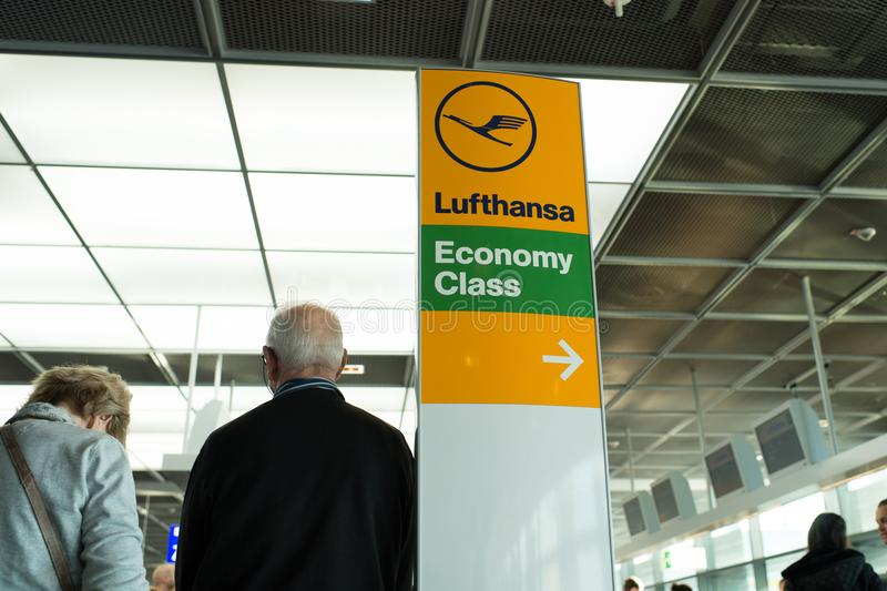 Frankfurt am Main, Germany - October 11, 2015: Lufthansa airlines logo icon, economy class and direction pointer sign. Airport inf royalty free stock photography