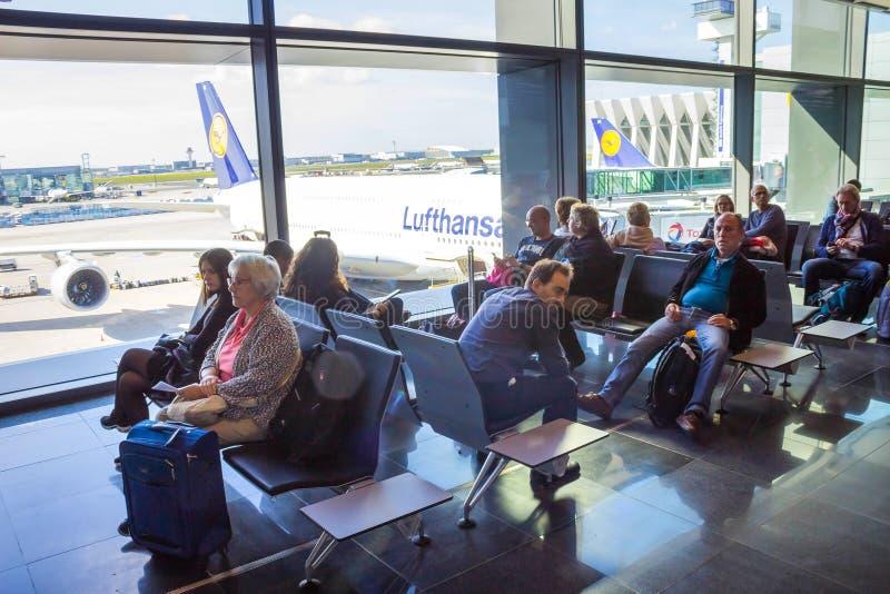 Frankfurt Niemcy, Kwiecień, - 28, 2018: pasażery siedzi odjazd wśrodku Frankfurt Pearson lotniska i czeka przy zdjęcie stock