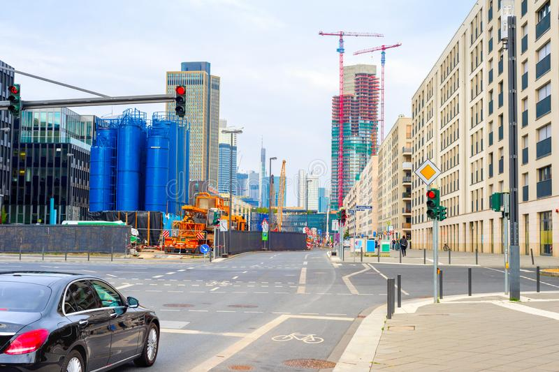 Frankfurt urban cityscape construction, Germany. Frankfurt urban cityscape with car on crossroad, industrial plant building, cranes by skyscraper construction stock image