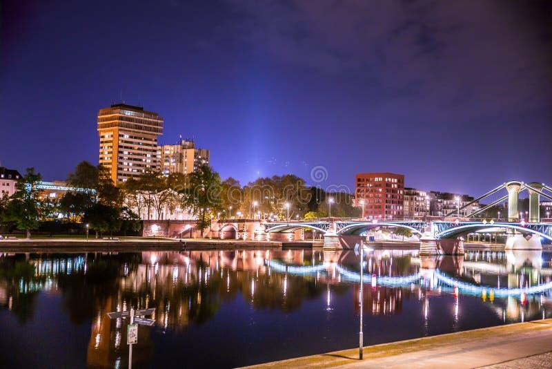 Frankfurt w Niemcy widzieć przy nocą z światłami, rzeką, budynkami i mostem, obrazy stock