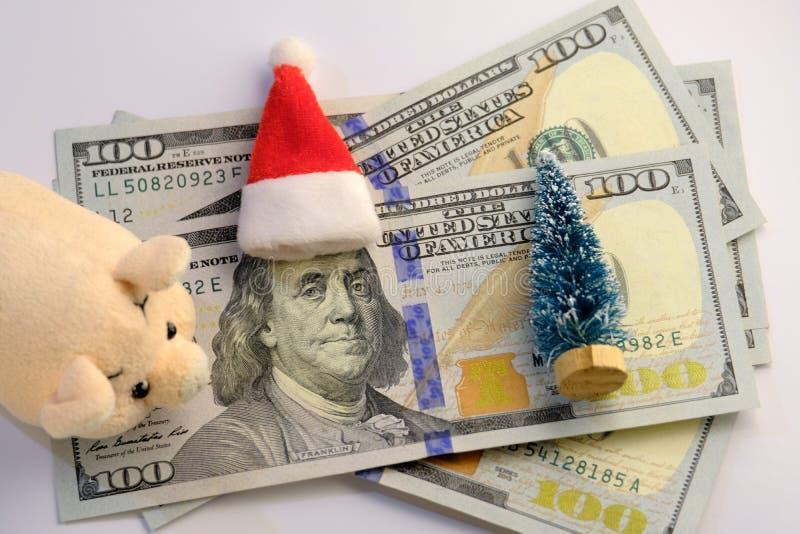 Franklin em cem dólares, em um leitão macio, em uma árvore de Natal e em um chapéu de Santa Claus Quanto dinheiro americanos gast fotos de stock royalty free