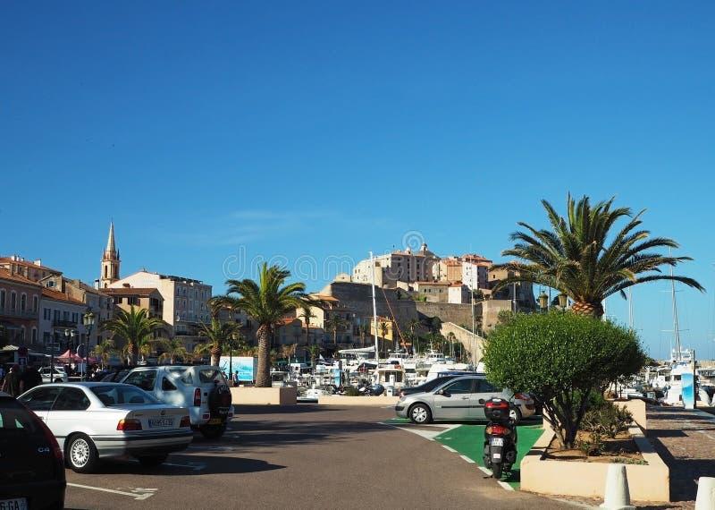 Frankrijk, Corse, Calvi, Juni, oude stadsmening van haven, jachthaven met jachten, auto's, kerk en citadele stock foto