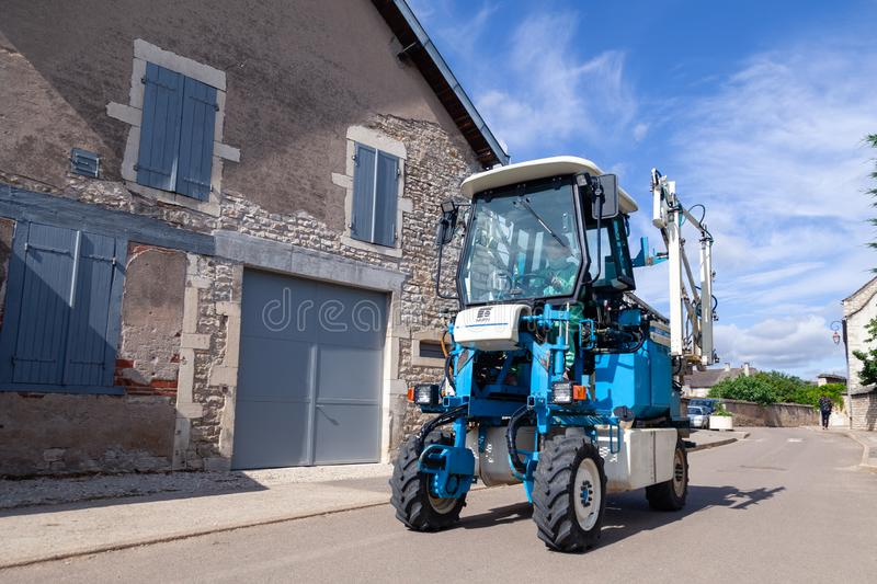 Frankrijk Lyon 2019-06-20 Winemaking equipment, vineyard harvesting machine, blue tractor Faupin Bobard met chauffeur op de dorps royalty-vrije stock afbeeldingen