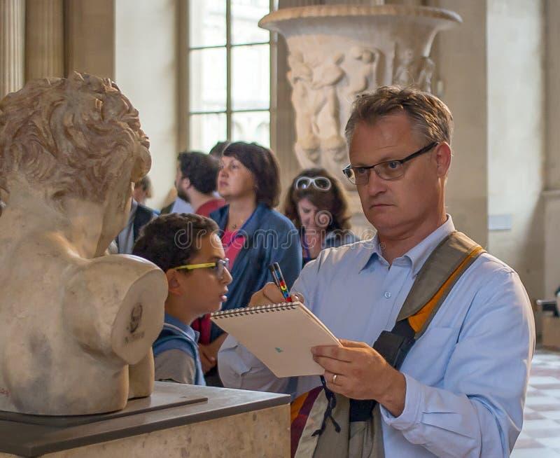 Frankrijk, Parijs 5 Augustus, 2017: Het Louvremuseum, een mens trekt een standbeeld van aard royalty-vrije stock afbeeldingen