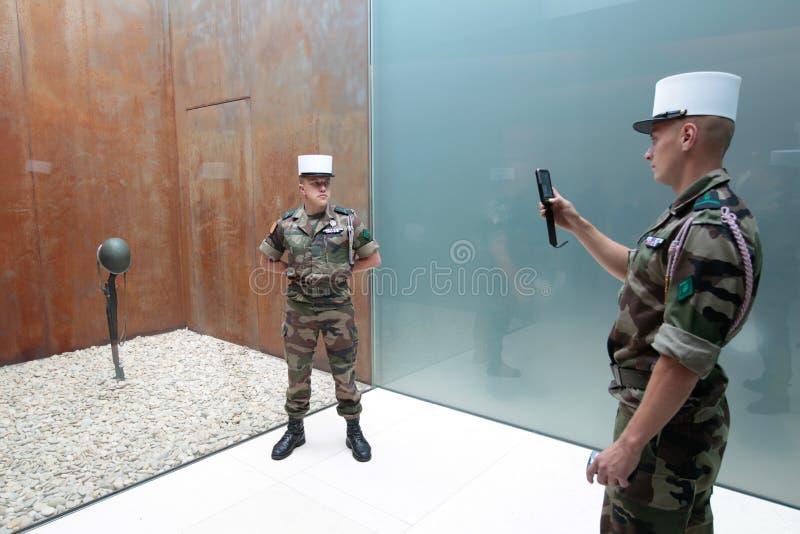 Frankrike Normandie, Juni 6, 2011 - två legionärer fotograferas med en amerikansk hjälm och plundrar royaltyfri fotografi