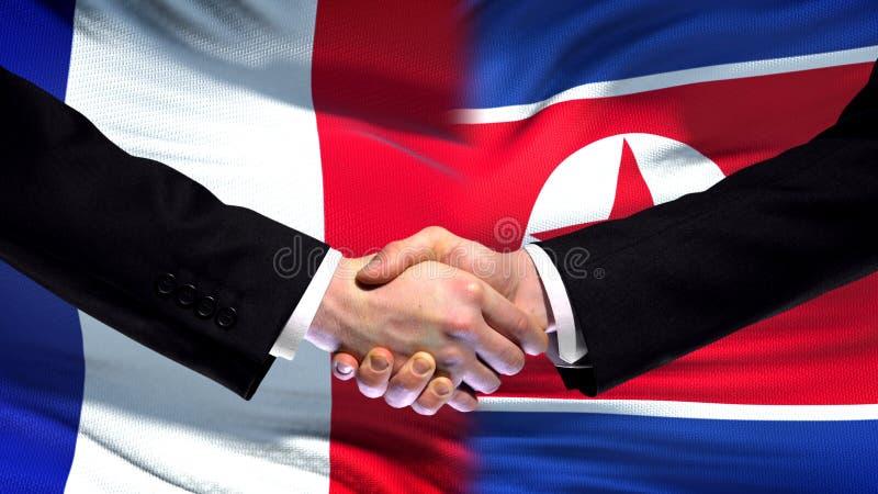 Frankrike och Nordkorea handskakning, internationellt kamratskap, flaggabakgrund arkivfoto