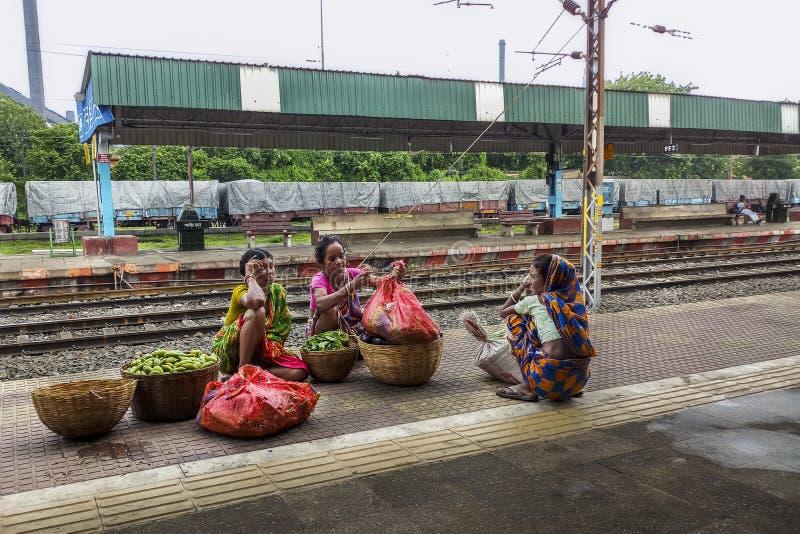 Frankt fotografi av några olyckliga fattiga indiska kvinnor som säljer grönsaker på plattformen av en stångstation royaltyfri bild