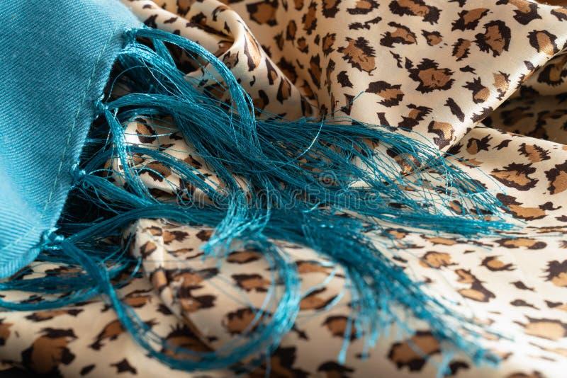 Frans av trådar på bakgrunden av tyg i färgen av leoparden arkivfoton