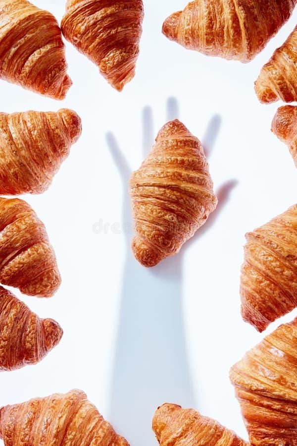 Frans croissantskader met handschaduw die bakkerij op een lichte achtergrond nemen stock fotografie