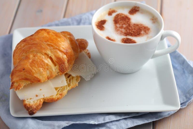 Frans ontbijt: croissantsandwich met kaas en koffie stock afbeeldingen
