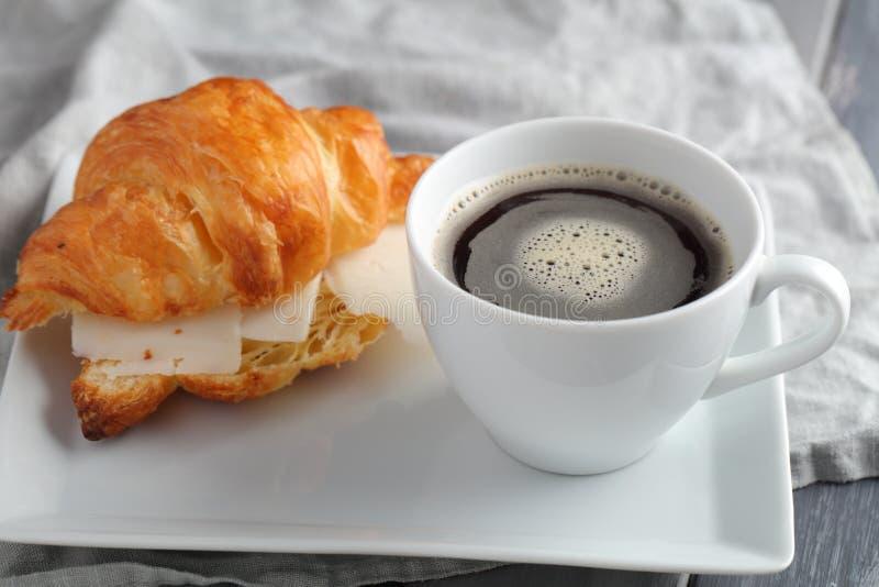 Frans ontbijt: croissantsandwich met kaas en koffie stock fotografie