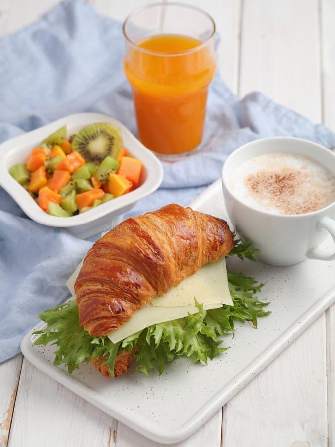 Frans ontbijt: croissantsandwich met kaas, fruitsalade, en koffie stock afbeeldingen