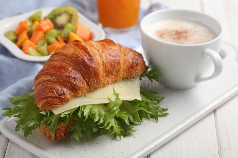 Frans ontbijt: croissantsandwich met kaas, fruitsalade, en koffie stock afbeelding