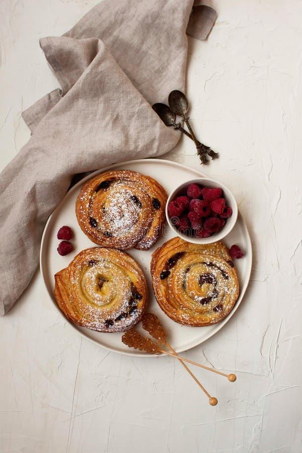 Frans ontbijt met kaneelbroodjes en frambozen stock foto's