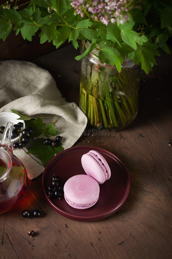 Franse blackcurrant macaron met roomkaas het vullen Stilleven met wildflowersboeket en bessenthee stock foto's