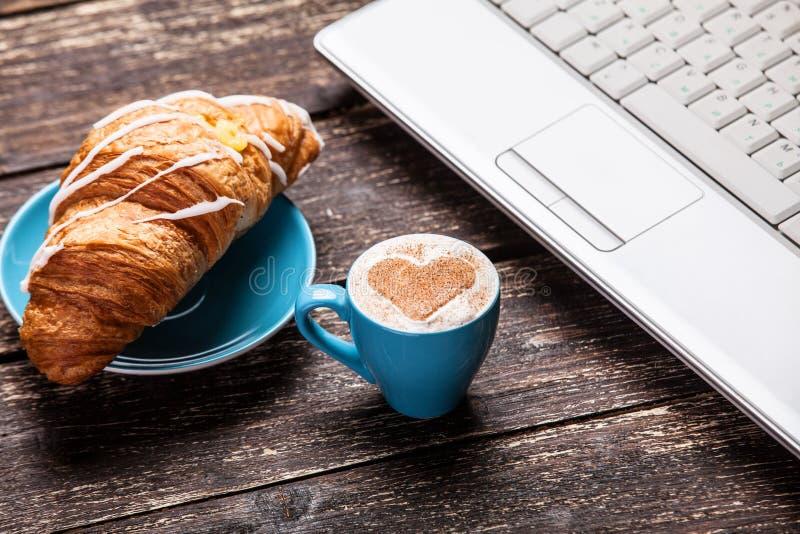 Franse croissant en kop dichtbij laptop royalty-vrije stock afbeelding