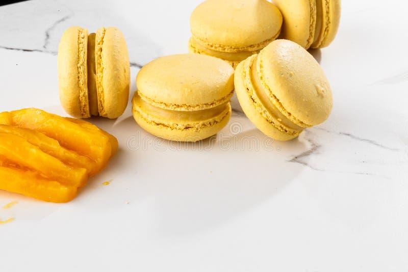 Franse geïsoleerde makarons Selectieve nadruk Mooie gele makarons met gesneden mango op marmeren achtergrond stylish stock afbeeldingen