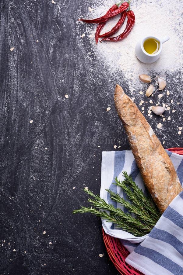 Franse gehele korrelbaguette in rode mand met Spaanse peperpeper, olijfolie, rozemarijn, knoflook en bloem op ruwe achtergrond De stock foto's
