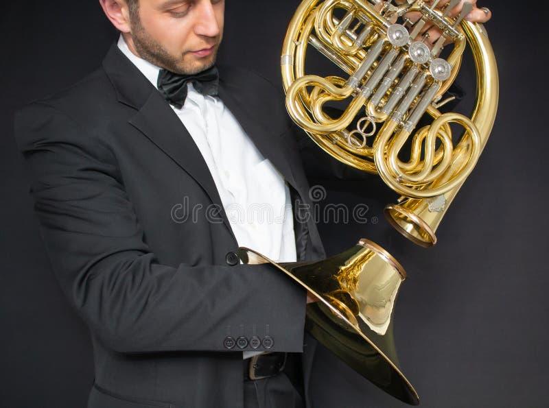 Franse hoornspeler De hoorn van het muziekinstrument in de handen van de hornista mens in een kostuum en in een vlinder met een m royalty-vrije stock fotografie