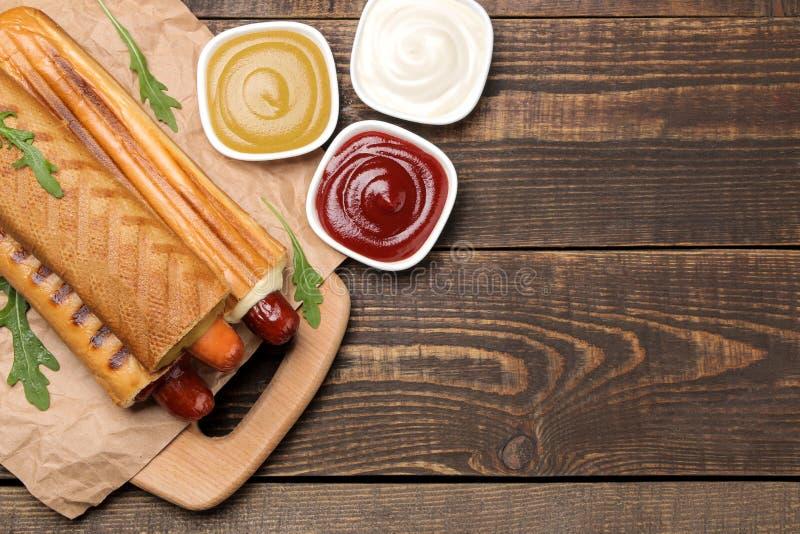 Franse hotdogs Smakelijke hotdogs op de raad en saus op een bruine houten lijst het voedsel van de snel voedselstraat Worsten in  stock foto