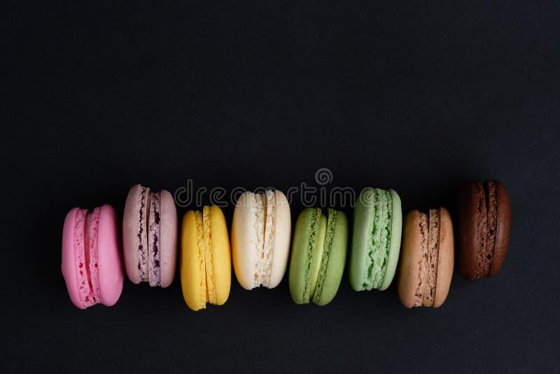 Franse makaronkoekjes op zwarte geïsoleerde achtergrond stock foto