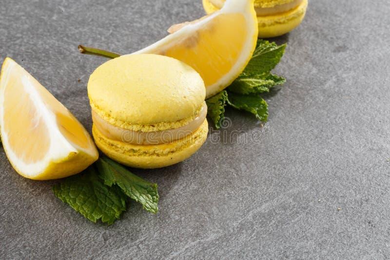 Franse makarons Selectieve nadruk Mooie gele makarons met citroen en munt op grijze steenachtergrond stock foto