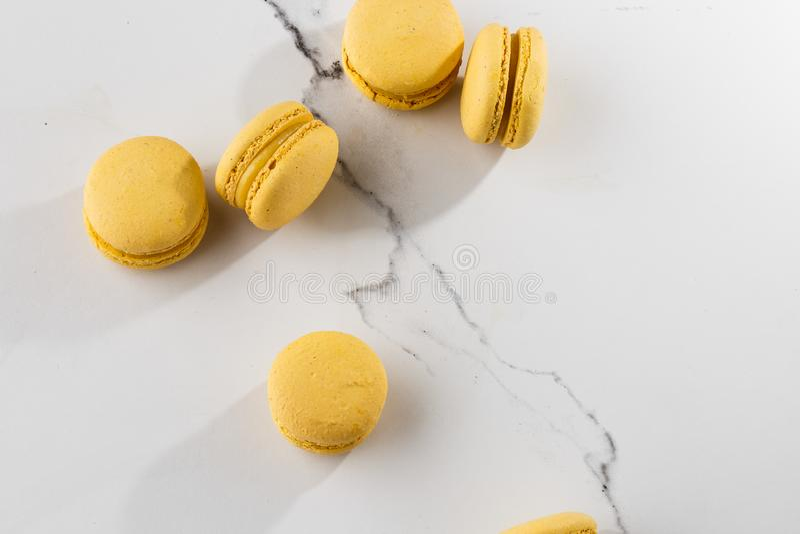 Franse makarons Selectieve nadruk Mooie gele makarons op marmeren achtergrond Modieus regelingssnoepje stock afbeelding