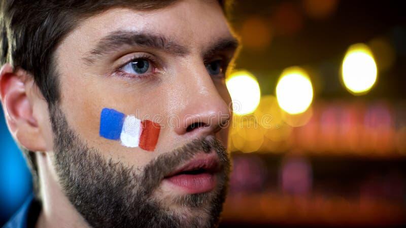 Franse mens met geschilderde vlag bij wang steunen nationaal tijdens harde tijden stock foto's