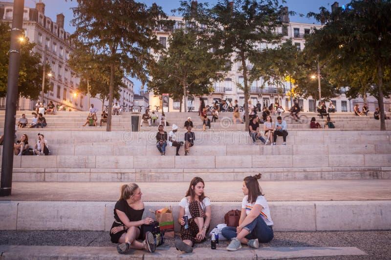 Franse mensen, hoofdzakelijk vrouwen en meisjes die op riverbank van quais van de Rhône in de avond zitten terwijl de mensen zich royalty-vrije stock fotografie