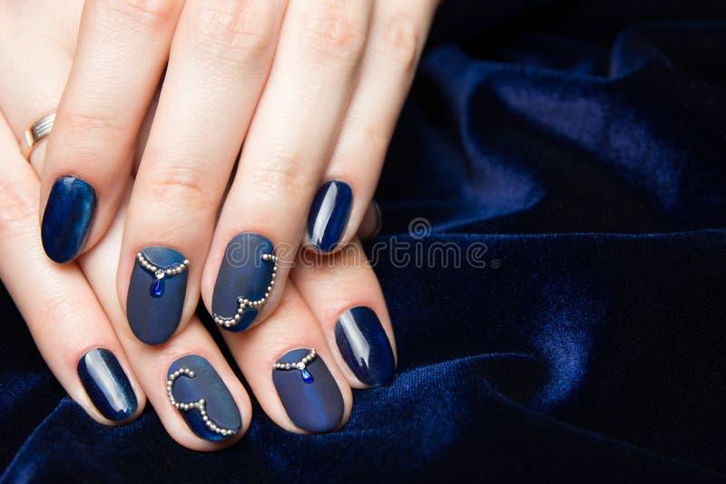 Franse mooie manicure - manicured vrouwelijke handen met blauwe manicure met bergkristallen op donkerblauwe achtergrond royalty-vrije stock afbeeldingen