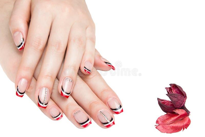 Franse mooie manicure - manicured vrouwelijke handen met rode zwart-witte die manicure met bergkristallen op witte achtergrond wo stock fotografie
