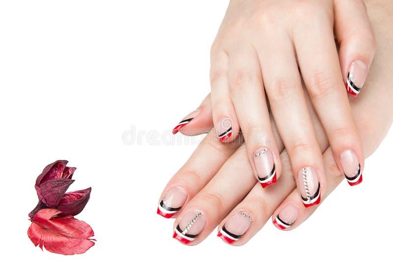 Franse mooie manicure - manicured vrouwelijke handen met rode zwart-witte die manicure met bergkristallen op witte achtergrond wo royalty-vrije stock afbeelding