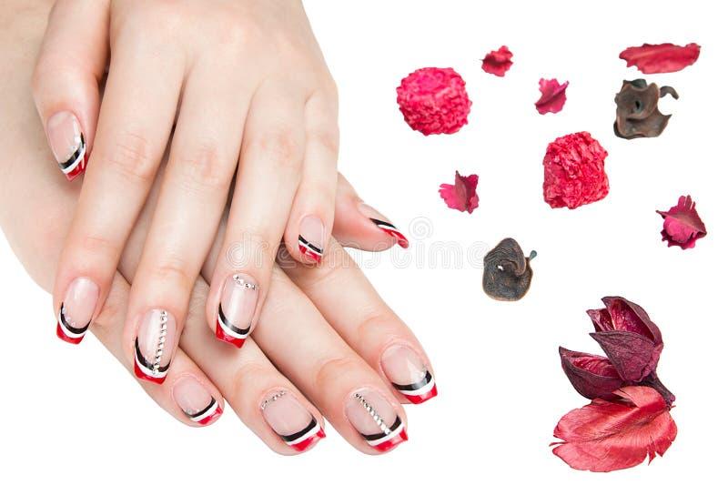 Franse mooie manicure - manicured vrouwelijke handen met rode zwart-witte die manicure met bergkristallen op witte achtergrond wo stock foto's