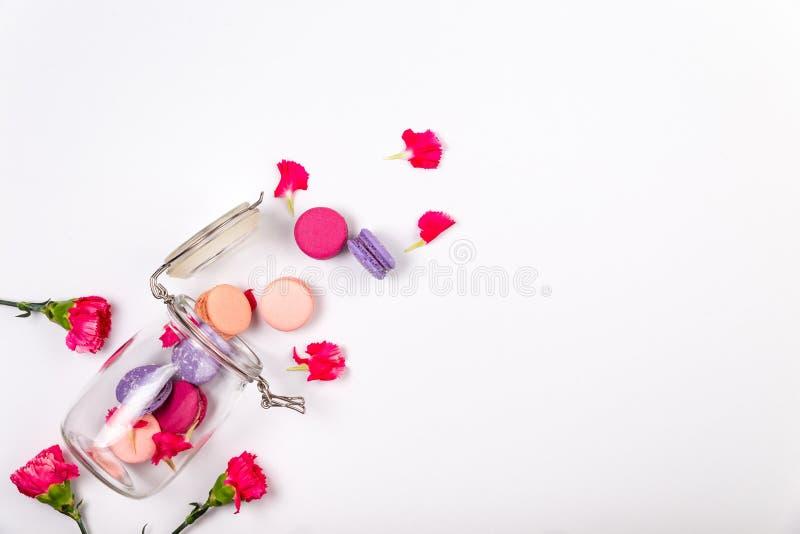 Franse roze en purpere macarons of makarons, roze incarnatiebloemblaadjes en bloemen die van een glaskruik uitvallen op een witte royalty-vrije stock foto
