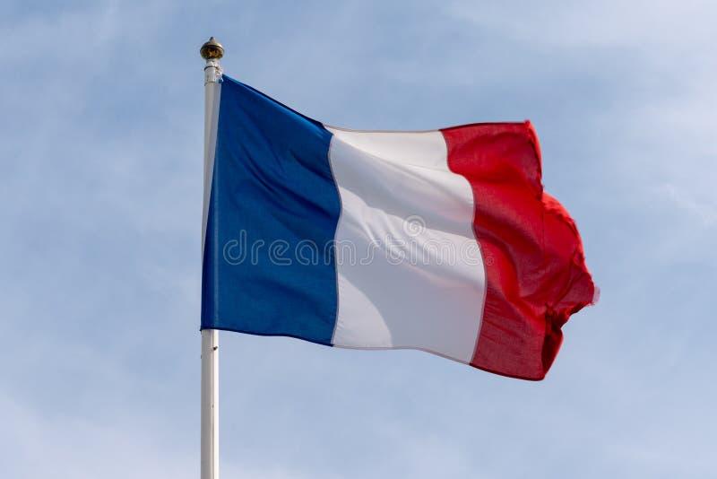 Franse vlag die van Frankrijk over bewolkte blauwe hemel blauwe witte rode kleuren golven royalty-vrije stock fotografie