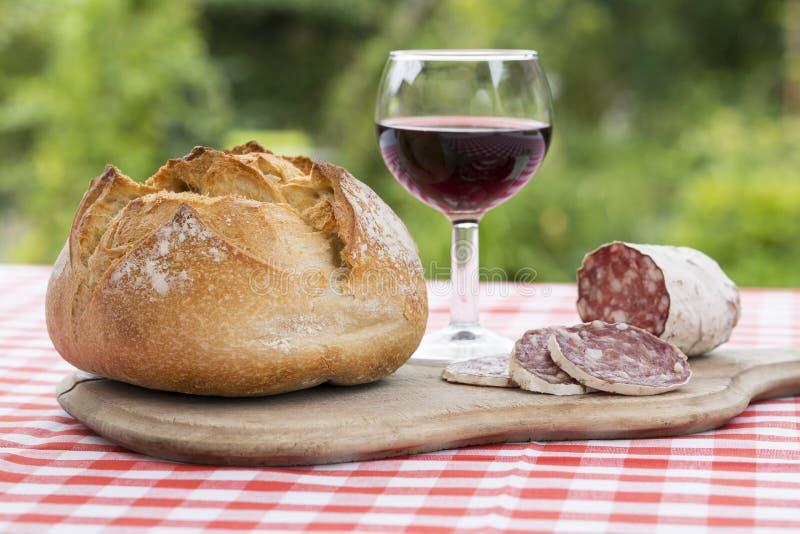 Franse worst op een houten raad met brood en rode wijn in een tuin stock fotografie