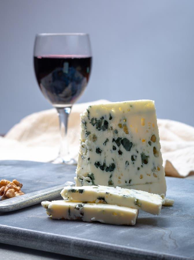 Fransk ädelostroquefort som göras från får, mjölkar i grottor av roquefort-sur-Soulzon och glas med rött vin arkivfoto