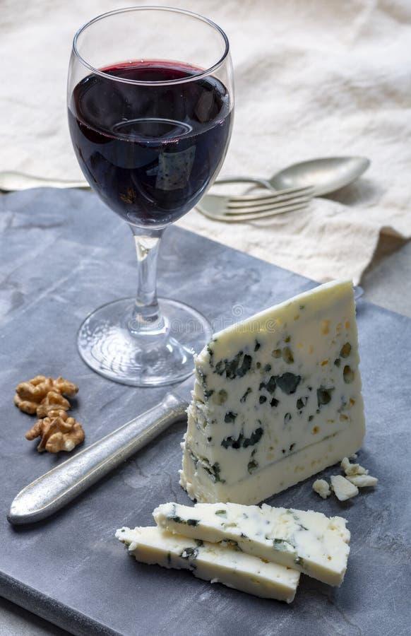 Fransk ?delostroquefort som g?ras fr?n f?r, mj?lkar i grottor av roquefort-sur-Soulzon och glas med r?tt vin arkivfoto