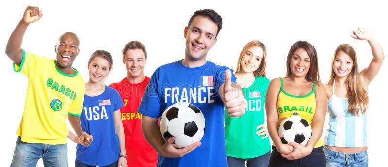 Fransk fotbollfan med fotbollvisningtummen upp med andra fans arkivfoton