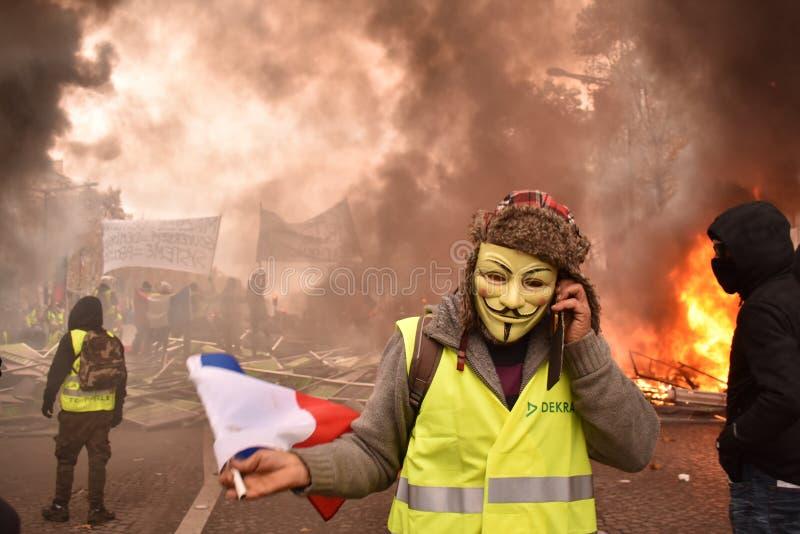 Fransk gul västprotesterare som bär den Guy Fawkes maskeringen på en demonstration i Paris royaltyfri foto