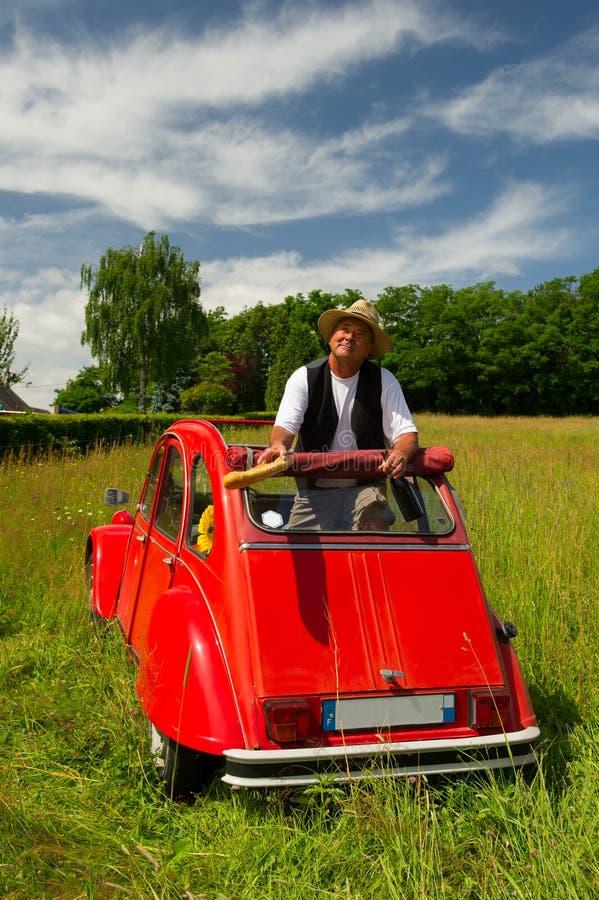 Fransk man med hans typiska röda bil royaltyfri fotografi