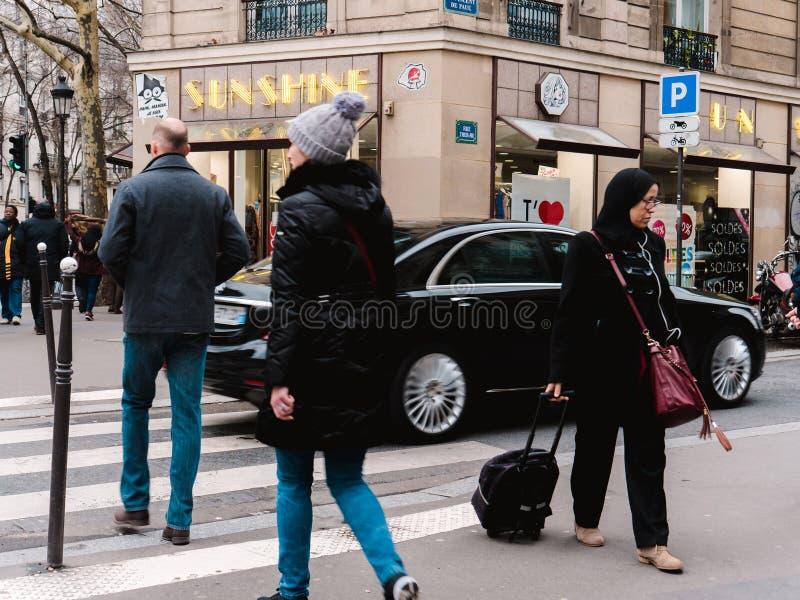 Fransk man- och kvinnligkorsning gata framme av Mercedes - Ben arkivfoto
